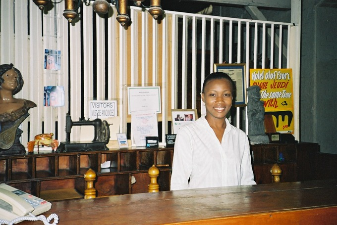 A hotel clerk stands behind the front desk.