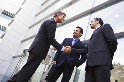 Businessmen talk and shake hands.