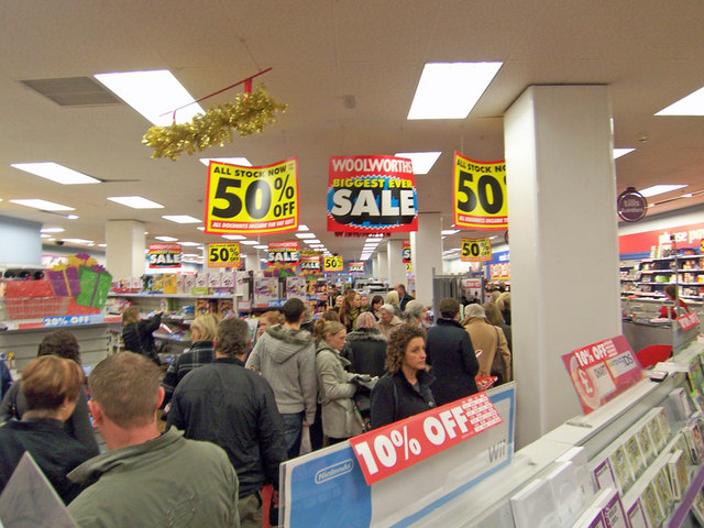 Customers shop in a store that has lots of different sale signs.