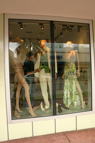 A retail store worker dresses mannequins in a store window.