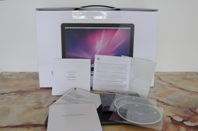 A photo of the pamphlets and CDs that come with an Apple product as part of the warranty.
