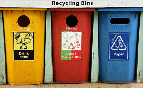 Three public trash cans that are used for recycling.
