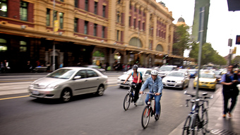 A man and woman ride bicycles in traffic.