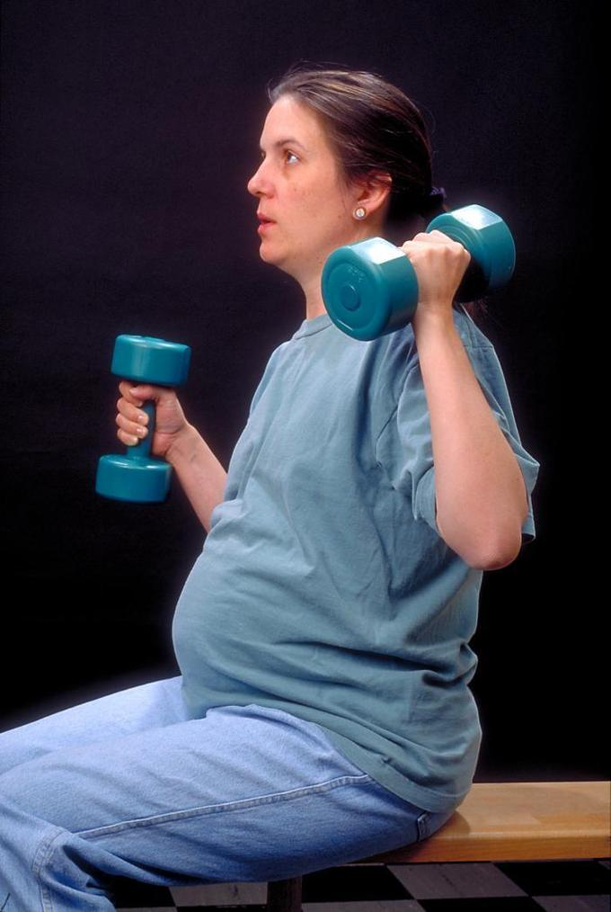 This is a photograph of a pregnant woman in gym clothes lifting hand weights. A strong, healthy woman will generally have a good pregnancy outcome. Physicians recommend moderate exercise during pregnancy, including strength-training.