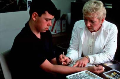 This image is of a young man receiving an allergy prick test. A blond-haired woman in a white lab coat sits on the right of the image. On her left is a young brown-haired man. His arm is out, and the woman, presumably a doctor, is pricking his skin with a tool. On the table in front of them is a tray of vials.