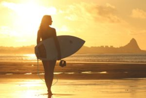 A woman walking on the beach at sunset holding a surfboard