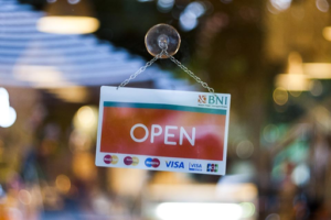 An open sign hanging on a glass window