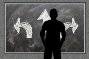 The silhouette of a man is shown standing before a chalk board. Three arrows are drawn on the board representing a choice that lies before the man.