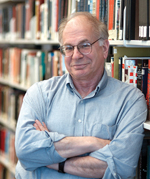 A photograph of Daniel Kahneman standing in front of shelves of books