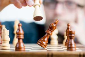 Man moving white chess piece while brown piece is falling