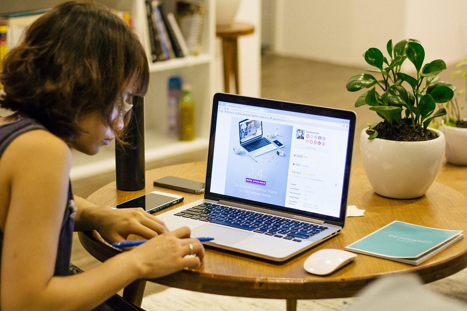 A woman sitting in front of a laptop at a table in her home