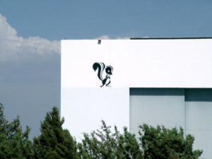 A white building with a cartoon skunk painted on the side, against a blue sky backdrop
