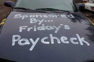 "The hood of a black car with the words ""Sponsored by… Friday's Paycheck"" on it."