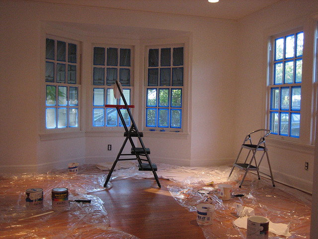 A white-walled room with two step stools, clear plastic, and several cans of paint on the floor