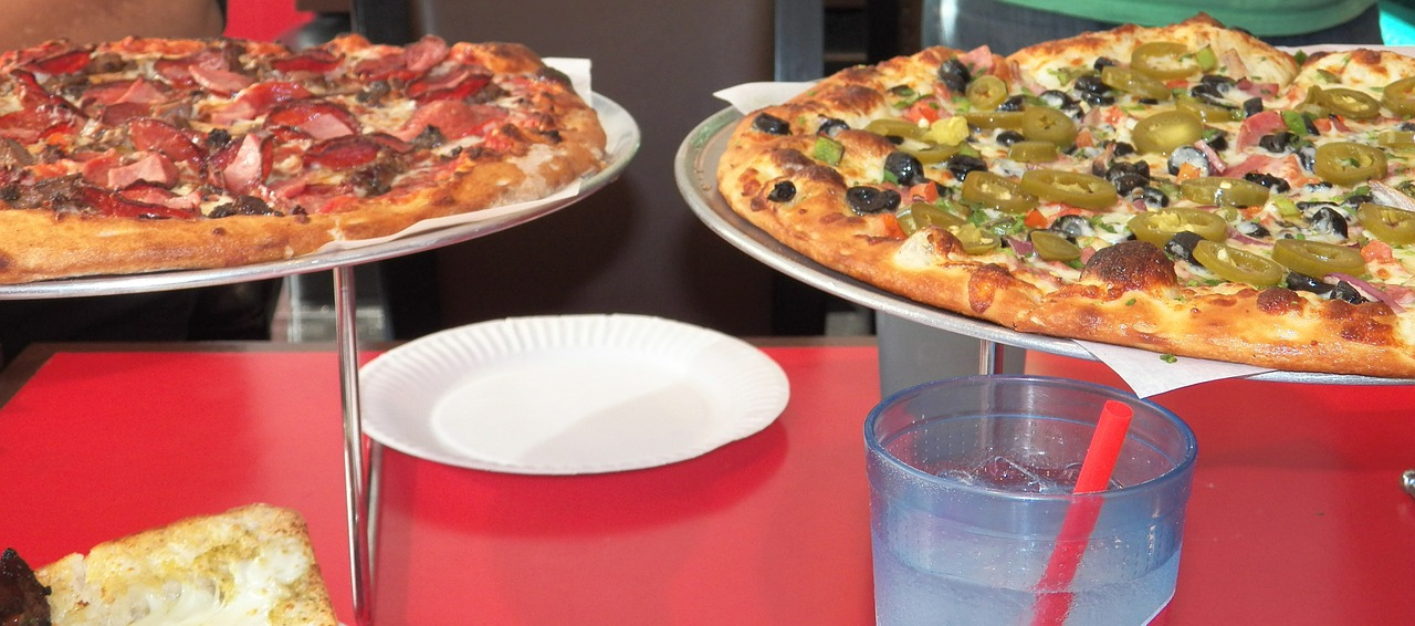 Two pizzas on racks on a red table