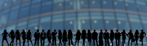 Silhouettes of many business people in front of a large building in the background.