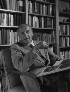 Peter Drucker, sitting on a chair, in a black and white photo.