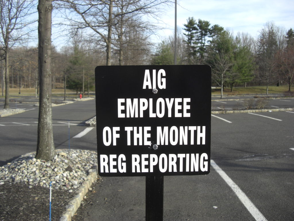In a parking lot, a sign that reads AIG Employee of the Month Reg Reporting