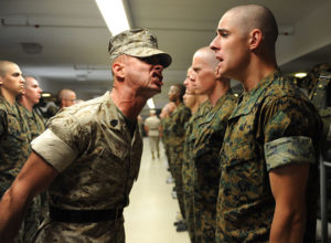 Drill instructor disciplining soldier with others standing at attention