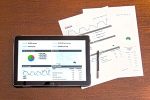 A tablet with analytical data on it and papers with data on a table