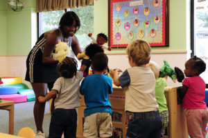Young lady playing with young children in a child care facility