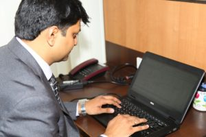 A businessman works at a desk on a laptop computer.