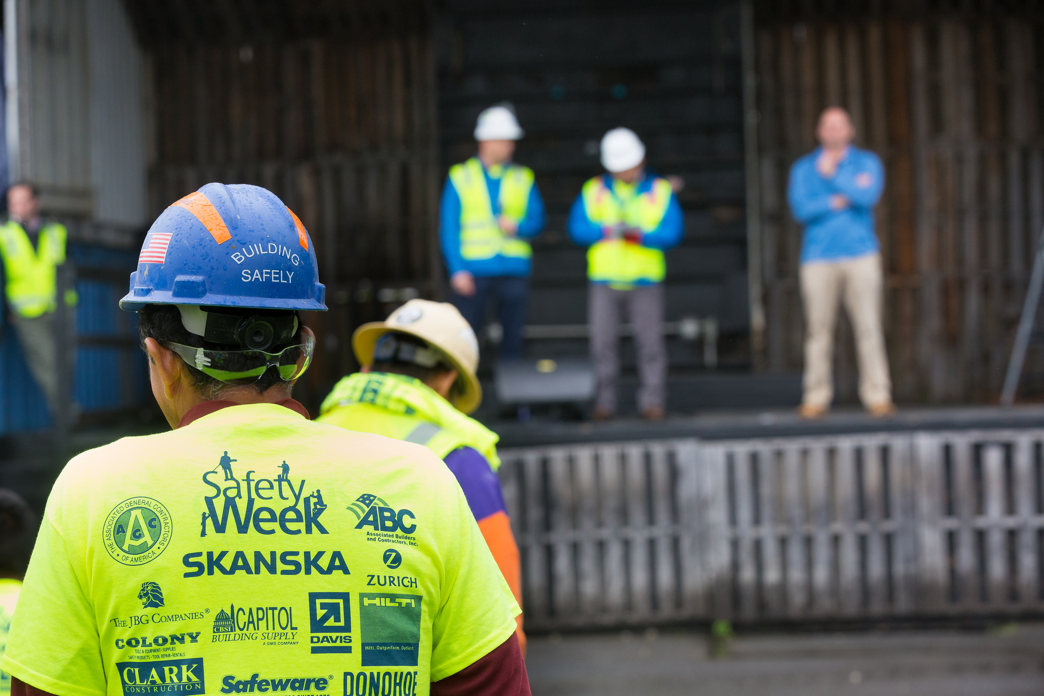 In the foreground, there's a worker wearing a hard hat and a yellow shirt that reads Safety Week. In the background, there are workers wearing hard hats and safety vests standing in an unfinished building.