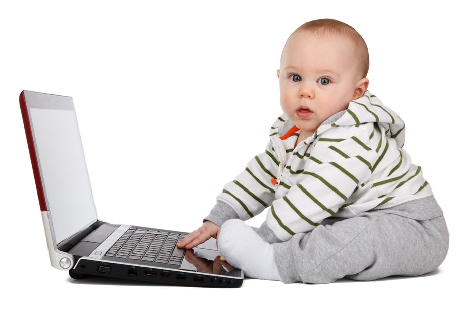 Baby appearing to type on a laptop