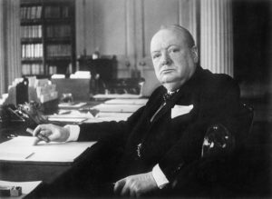 Winston Churchill sitting at a desk looking towards the camera