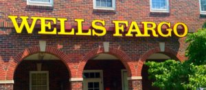 Picture of the front of a brick building with arches with the Wells Fargo name is large yellow letters.