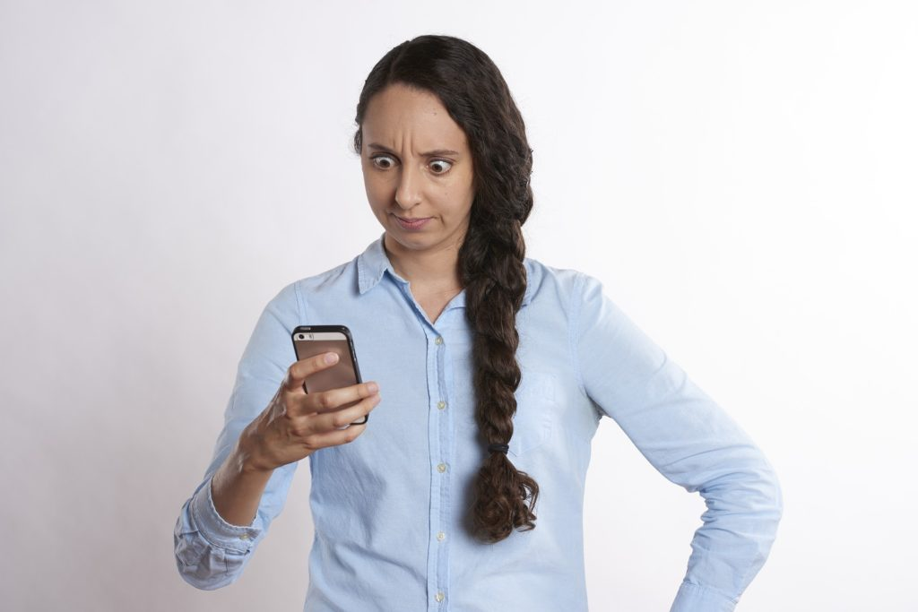 Photograph of a woman looking at a mobile phone. She looks upset and a little surprised.