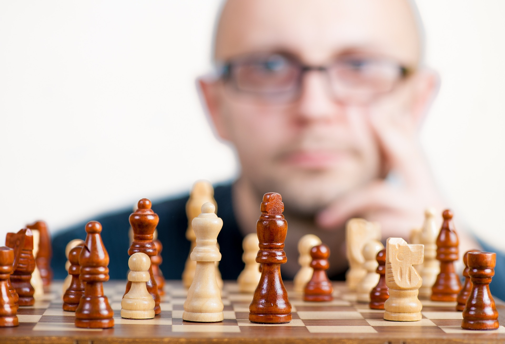 Pieces set up on a chess board, with a man appearing out of focus in the background with a thoughtful expression on his face