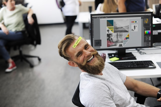 "A male employee sitting in front of a computer, dressed casually and smiling at the camera. He has a sticker on his forehead that reads ""Be Happy."""