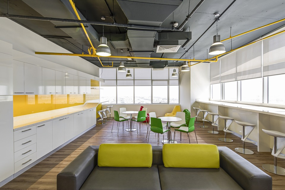 A large space in a modern looking office building with a couch, tables and chairs, and counter space.
