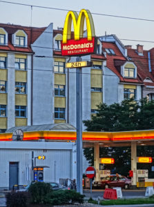 A McDonald's sign with a gas station and residential building in the background.