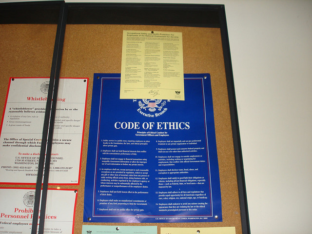 A bulletin board showing documents on whistleblowing and the Code of Ethics from the US Sentencing Commission