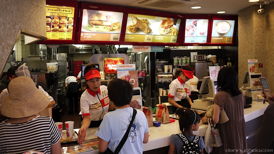 The counter at a busy McDonald's restaurant, with employees taking orders from customers and delivering food.
