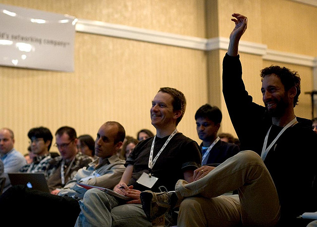 Two men sit in an audience and one man has his hands raised to ask a question.