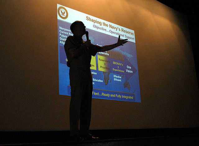 A picture of Commander Naval Reserve Force Vice Adm. John G. Cotton in front of a Powerpoint slide. He is mapping out the Naval Reserve Force's future.