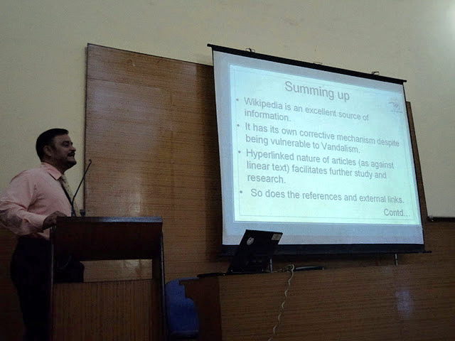 A picture of a speaker showing the last slide in a presentation during the Wiki Conference in India.