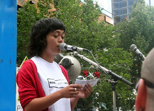 A picture of a young woman talking into a microphone during a public speech at a park.