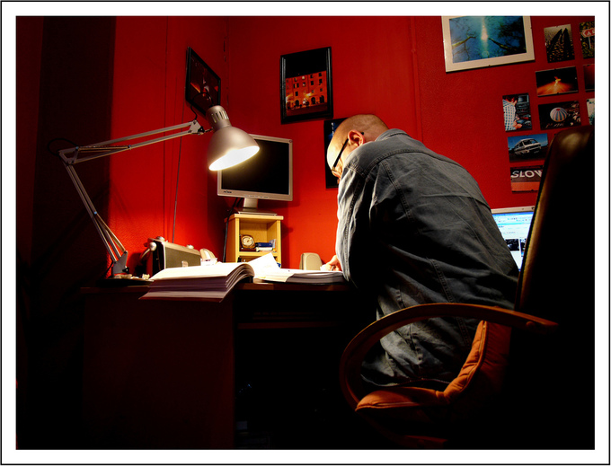 A picture of a man sitting at a desk and reviewing research material.
