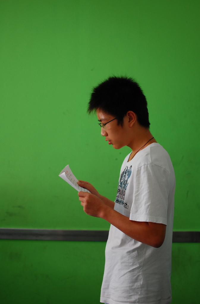 A picture of a man holding a piece of paper and practicing his speech.