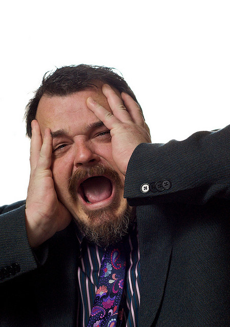A picture of a man putting his hands on his face and making a nervous expression.