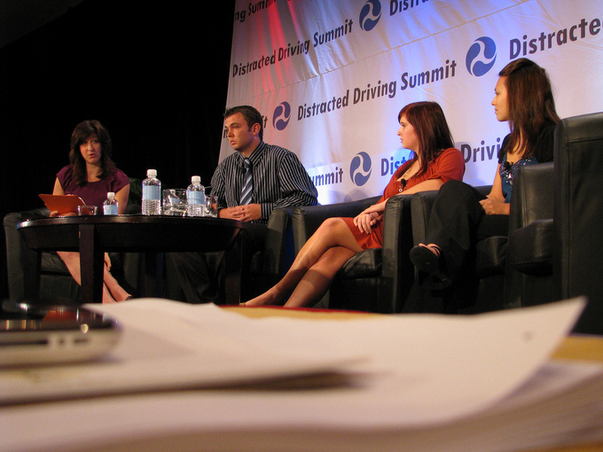 A picture of four panelists sitting at a small table. One panelist is talking while the others listen.