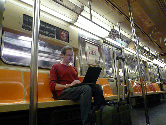 A picture of a man using his laptop while he's riding on a subway train.
