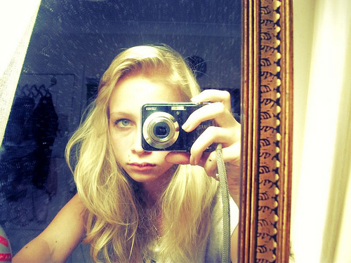 A girl taking a picture of herself in a mirror.
