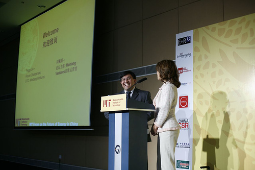 Two speakers are standing in front of a podium during the MIT Energy Innovation Panel.