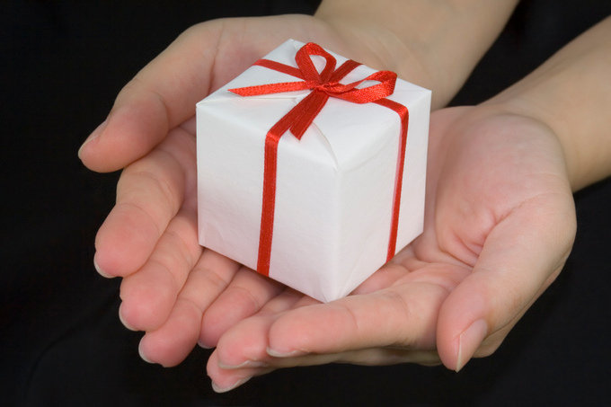 A woman holds a small present in her hands.