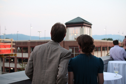 A man and woman looking into the distance from a rooftop restaurant.